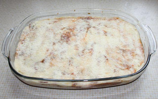 Für die Gemüselasagne schichte die Soßen und die Teigplatten abwechseln in die Auflaufform.