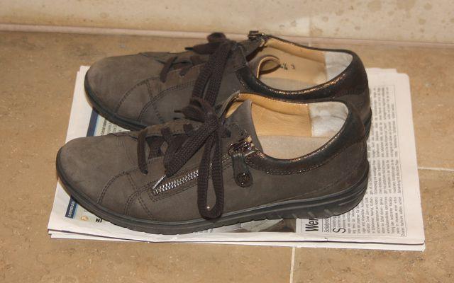 Alte Zeitungen schützen den Boden vor dem Schmutz auf Schuhen.