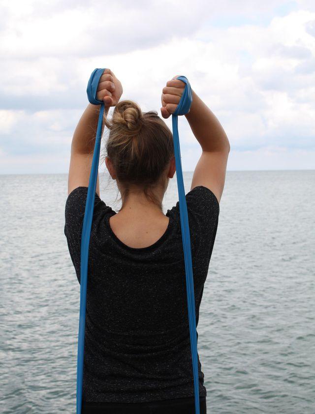Diese Trizeps-Übung kannst du entweder mit einem elastischen Band oder Kurzhhanteln ausführen.