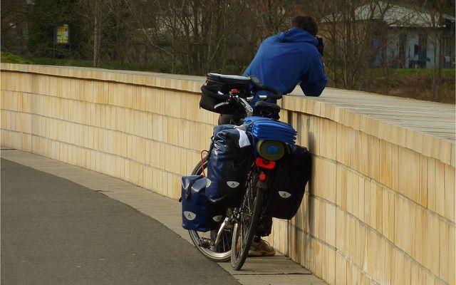 Fahrradurlaub: Radler lehnt mit Fahrrad an Mauer