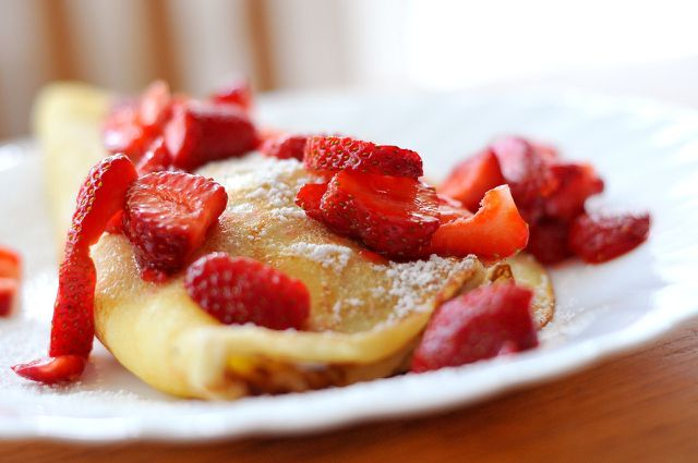 Serviere deine gefüllten Pfannkuchen mit Quarkcreme am besten noch warm.