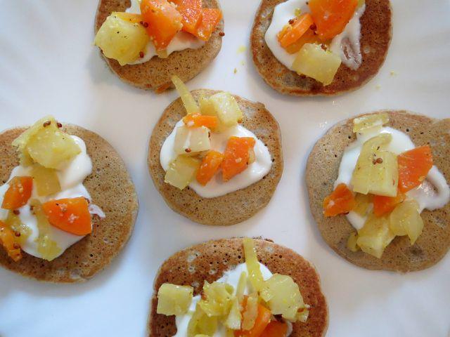 Blinis schmecken lecker mit einem Klecks saurer Sahne und gebratenen Gemüsewürfeln.