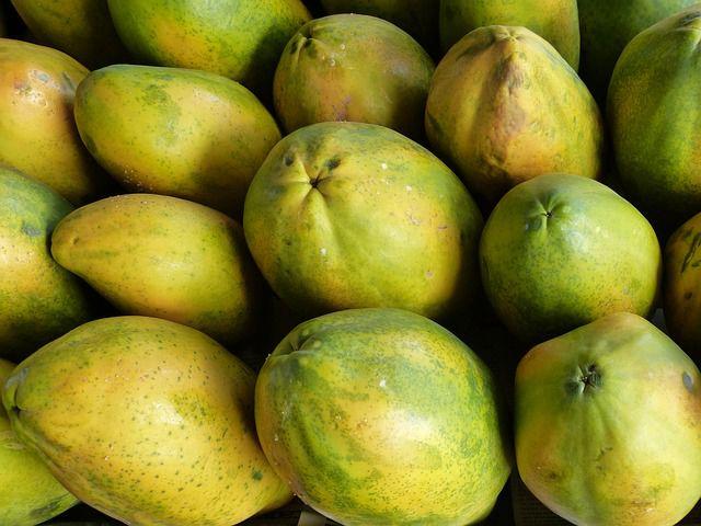 Die Schale einer reifen Papaya ist gelb-grün.