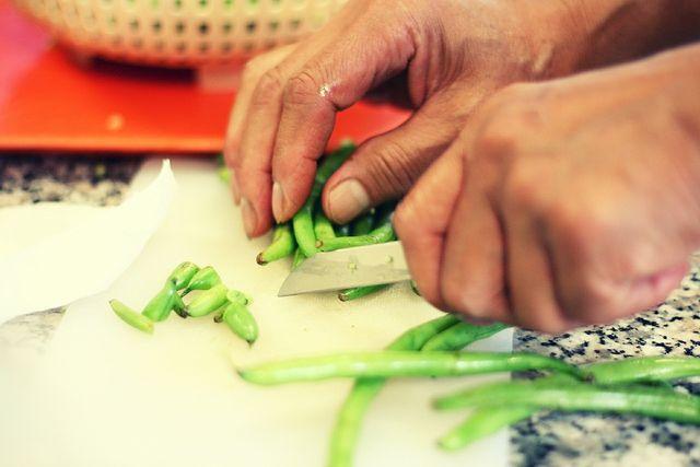 Entferne die Spitzen der Bohnen mit einem Messer.