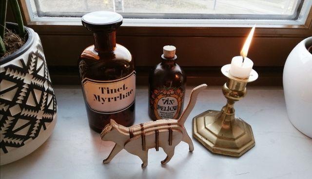 Gebrauchte Deko: Alte Apothekenfläschchen, Vintage-Kerzenständer und DIY-Katze sind individuelle Deko-Objekte.