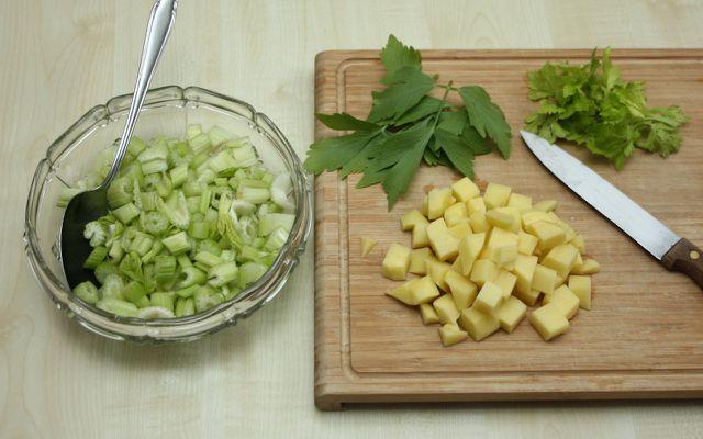 Für die Staudensellerie-Suppe schneide zuerst alle Zutaten in kleine Stücke.