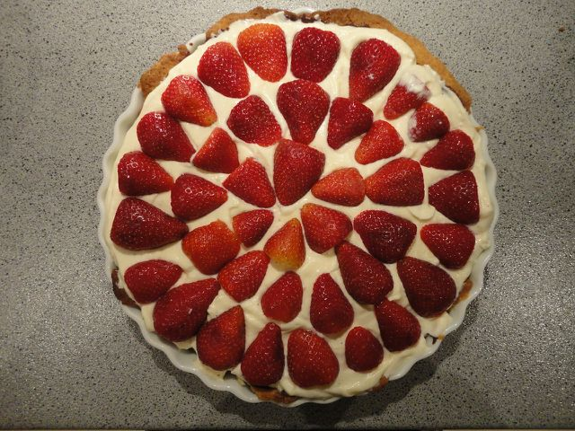 Ein veganer Erdbeerkuchen sieht besonders lecker aus, wenn du die Erdbeeren gleichmäßig platzierst.