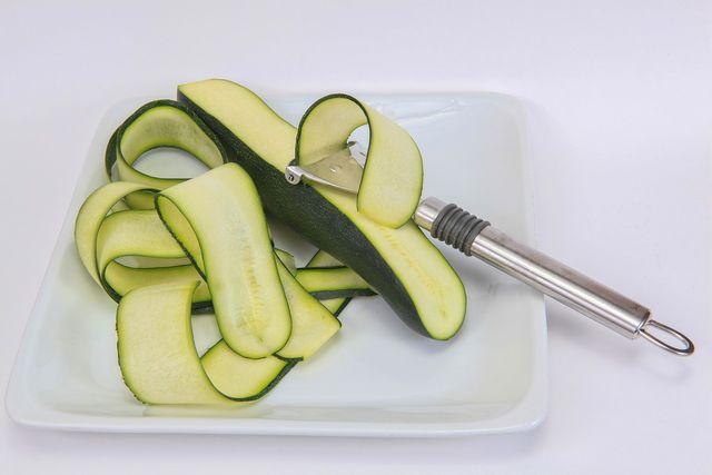 Zucchini kannst du auch mit einem Sparschäler in feine Scheiben schneiden.