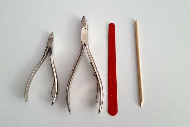 Nagelhautzange, Nagelzange, Feile und Rosenholzstäbchen sind wichtige Utensilien für die Nagelpflege.