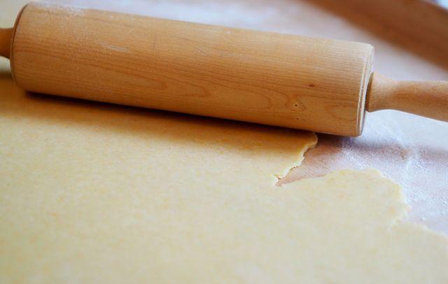 Rolle den Teig mit einem Nudelholz zu dünnen Teigplatten aus.