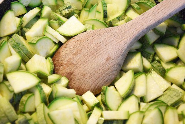 Für das Zucchinirisotto schneidest du die Zucchini in kleine Stücke.