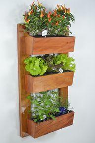 Gewinne mehr Platz im Balkongarten durch vertikale Pflanzkästen an der Wand.
