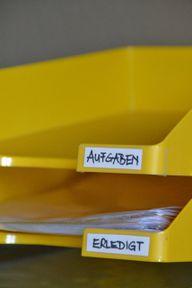 Organisiere Papiere auf dem Schreibtisch, um den Überblick zu behalten.