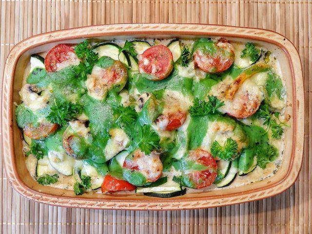 Zu deinem veganen Auflauf passen Tomaten und frische Kräuter als Topping.