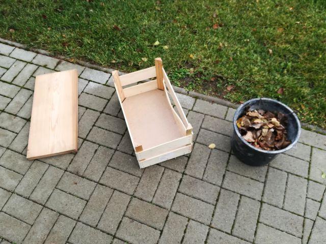 Ein Holzbrett, eine Obstkiste und Herbstlaub: die Grundmaterialien für das Igelhaus.