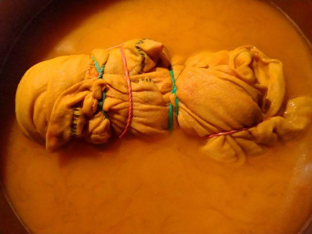 Mit Gummibändern fixiertes Batik-Shirt in Kurkuma-Farbbad.